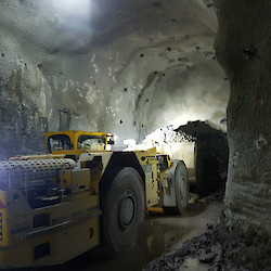 Scoop truck loading muck in underground mine decline